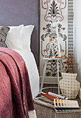 Bed, white bedside table and lamp against patterned wallpaper