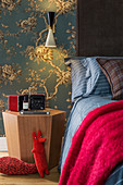 Reading lamp on hexagonal bedside table and bed against floral wallpaper