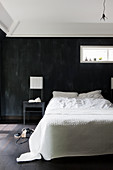 Double bed with white bed linen against black wall