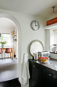 Base cabinet and wall clock next to arched open doorway in kitchen