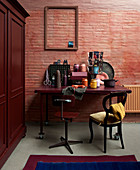 Desk and chairs against dusky pink brick wall with wooden cupboard on one side