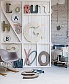 Weißes Holzregal mit Dekobuchstaben