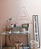Vintage desk and chair below decorative letter on pink wall