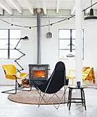 Outdoor chairs in black and yellow in front of wood burner in living room