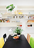 Black table and colourful chairs below crockery on white shelves