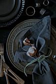Stoffserviette mit Baumwollkapseln und Samtband auf Silberteller