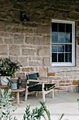 Stuhl und Beistelltisch auf der Terrasse am Haus aus Naturstein