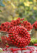 Wreath of crab apples and basket of chrysanthemums
