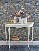 Flowers on console table against vintage-style floral wallpaper