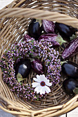 Wreath of flowering thyme, aubergines and flower in basket