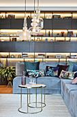 Illuminated shelving in elegant living room with corner sofa