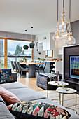Open-plan kitchen in modern, multifunctional interior decorated in grey