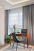 Grey upholstered chair and desk opposite window with grey curtains