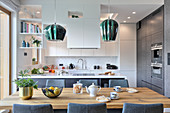 Upholstered chairs around wooden table in front of open-plan kitchen in white and grey