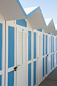 Blue-and-white changing cubicles on beach at Fano (Italy)