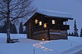 Beleuchteter Weg im Schnee zur alpinen Hütte am Abend