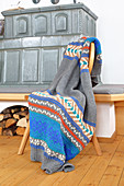 Knitted blanket with Norwegian pattern next to tiled stove