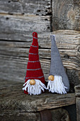 Knitted winter decorations in shapes of gnomes on rustic wood