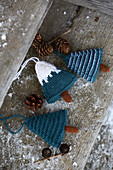 Knitted winter decorations in shapes of fir trees on rustic wood