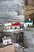 Knitted winter decorations in shapes of houses on snowy wood