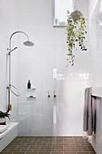Duschbereich im Badezimmer mit weißen Wandlfiesen