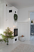 Small Christmas tree next to tiled stove in white living room