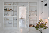Fitted shelving surrounding door in classic, white living room