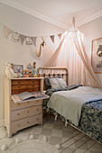 Antique bureau and metal bed in vintage-style child's bedroom