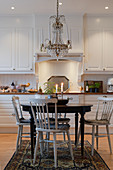 Spoke-back chairs at round table in classic, white kitchen