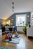 Christmas tree in child's bedroom with blue walls and sloping ceiling