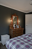 Antique chest of drawers with mirror against dark wall in bedroom