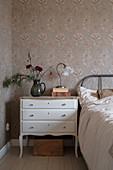 Vintage-style bedside cabinet in granny-chic bedroom