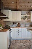 White country-house kitchen with wooden ceiling and tiled floor