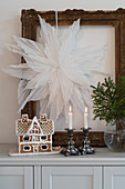 Gingerbread house and candles below paper star in gilt picture frame