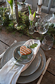 Place setting decorated with heart-shaped biscuit and eucalyptus sprig on set table