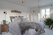 Grey fur on bed with valance in shabby-chic bedroom