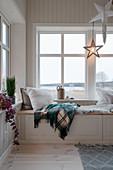 Gemütlicher Sitzplatz auf der Truhenbank am Fenster im Winter