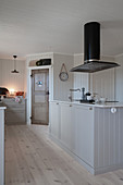 Kochinsel in skandinavischer Landhausküche in Weiß und Grau