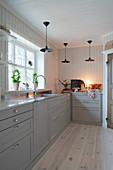 Scandinavian country-house kitchen decorated in white and grey with wood-clad walls