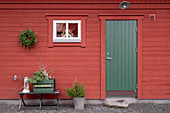 Falu-red Swedish house with green wooden door and simple winter decorations