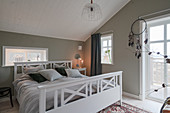 White bed in grey bedroom with balcony