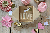 The word 'Home' made from letters in paper box surrounded by handmade paper decorations