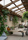 Beer-garden benches used as partition in conservatory with brick walls