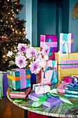 Bunt verpackte Geschenke mit glitzerndem Papier und Dahlienstrauß