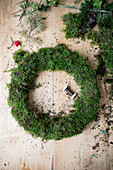 Handmade moss wreath on wooden table