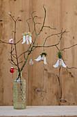 Engel aus Holz mit Papierflügeln und Haaren aus Kiefernadeln und Moos