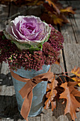 Ornamental cabbage and sedums in metal vase with brown ribbon