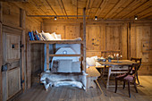 Loft bed above masonry stove and dining table in rustic farmhouse parlour