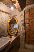 Oval, gilt-framed mirror in rustic bathroom of farmhouse