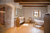 Free-standing bathtub in large bathroom of rustic farmhouse
